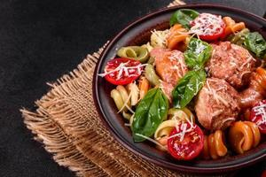 deliciosa pasta fresca con albóndigas, salsa, tomates cherry y albahaca foto