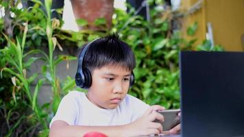 Asian boy wearing headphones playing a game on his smart phone. video