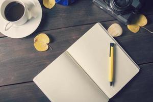 café y taza en un plato y un libro de recuerdos en blanco con cámara retro foto
