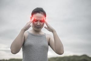 Young beautiful Asian woman with a headache photo