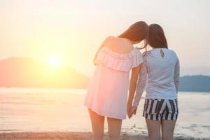Two young women hold hands together on the beach looking at sunset photo