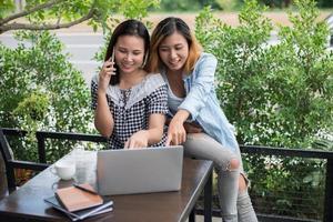 Dos hermosas mujeres jóvenes en busca de información en la computadora portátil foto