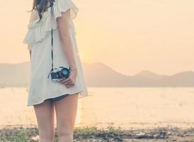 Beautiful woman photographer standing hand holding a retro camera photo