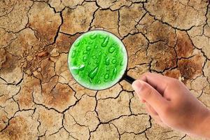 mano que sostiene la lupa para encontrar agua en la tierra seca y agrietada foto