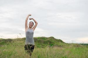 Young beautiful woman spreading hands with joy and inspiration at meadows photo