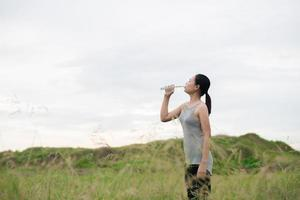 Beautiful young woman drinking water after training yoga at meadows photo