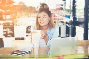 mujer joven inconformista sosteniendo una taza de café y trabajando un poco. foto