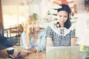 dos amigos disfrutando de trabajar juntos en una cafetería. foto