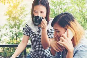 dos amigos sonrientes disfrutando trabajando juntos en una cafetería. foto