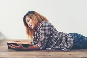 Young hipster woman reading book lay down on wooden floor at home. photo