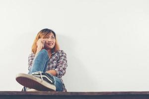 Happy hipster woman sitting on wooden floor talking with phone photo