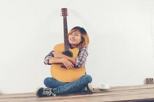 Beautiful woman sitting with her guitar happy sitting on the wooden photo