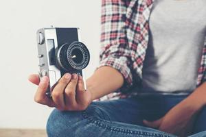 Young hipster photographer woman taking photo and look at camera