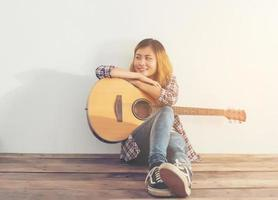 Hipster woman style portrait chillin with guitar look so happy. photo