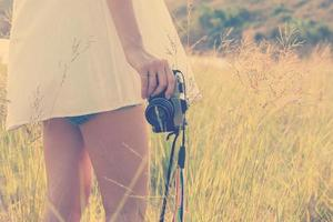 Young woman hand holding retro camera close-up photo