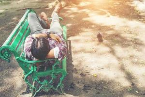 Young hipster man lying down on green park bench, looking away. photo