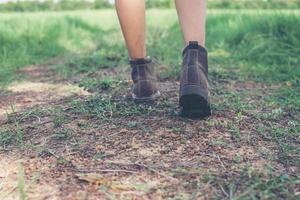 Pies de mujer joven aventura caminando sobre grava en el campo. foto