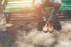 Hipster guy sitting on bench with  jeans and brown chamois shoes. photo