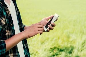 primer plano de las manos del hombre con su teléfono inteligente al aire libre en el parque. foto