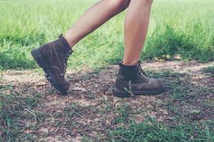 Pies de mujer joven aventura caminando sobre grava en el bosque. foto