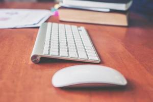 teclado inalámbrico, ratón en la mesa de madera de la persona de negocios. foto