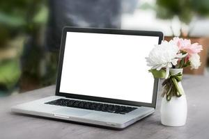 Laptop with blank screen on table and flower photo