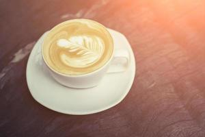Taza blanca de café capuchino con espuma de leche en forma de árbol foto