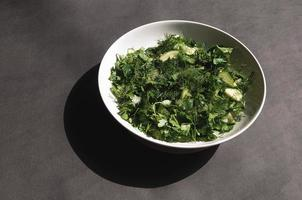 Salad with dill and parsley cucumbers on plate a gray background photo