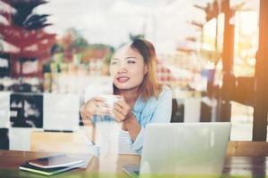 Mujer inconformista sosteniendo una taza de café y trabajando en el café foto