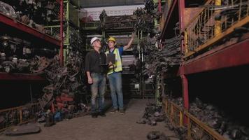 une paire d'ingénieurs masculins vérifiant les pièces du moteur dans un entrepôt video