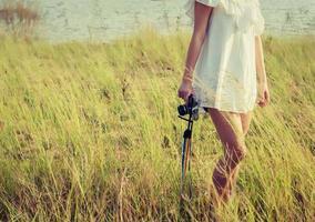 Beautiful woman photographer standing hand holding retro camera photo