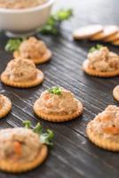 Tuna spread with cracker on wood board photo
