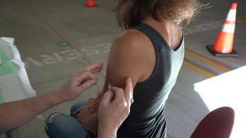 Enfermera aplicando vendaje después de la vacunación. video