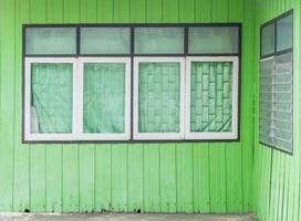 Old window on green wood wall photo