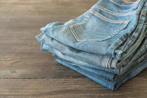 Stacks of jeans clothing on wood background photo