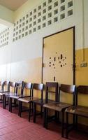 Silla de estudiante sin usar frente a la puerta rota de un aula vieja foto