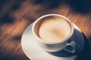 cup of coffee  on table in cafe in dark tone and vintage photo