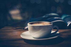 cup of coffee with magazine on table in cafe in dark tone and vintage photo