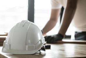 Centrarse en el casco de seguridad en la mesa de trabajo y carpintero en la mesa foto