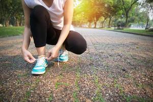 runner tying running shoe on way in park photo