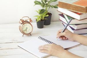 hand writing paper on desk and work place with clock, book and palnt photo