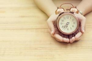 hand holding alarm clock on wood table photo