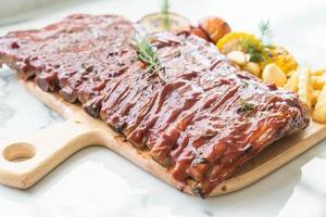 Costilla de cerdo a la parrilla con salsa barbacoa y verdura foto