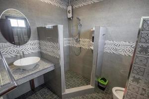 Baño blanco moderno y de madera con cabina de ducha de vidrio en el apartamento foto