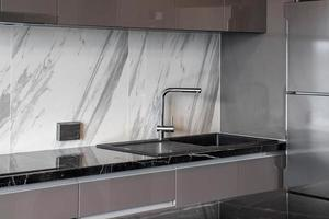 Clean stainless steel sink. small kitchen counter in the apartment. photo