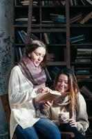 Cute student friends reading books together having fun photo