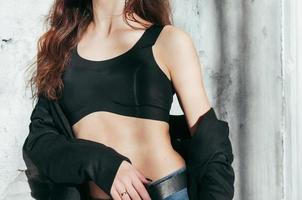 Fit girl in a black jacket and bra, fashion photo
