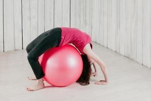a girl making a bridge pose over a pink fitball in a gym photo