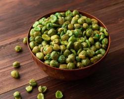 Salted green peas in wooden bowl on the table photo