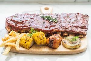 Costilla de cerdo a la plancha con salsa barbacoa y patatas fritas y verduras foto
